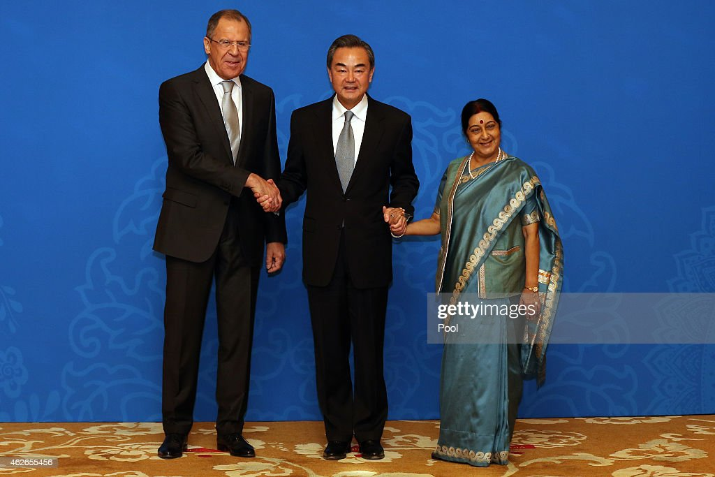 Russian Foreign Minister Sergei Lavrov (L), Chinese Foreign Minister Wang Yi (C) and Indian Foreign Minister Sushma Swaraj (R) shake hands before the 13th trilateral meeting of Foreign Ministers from Russia, India and China (RIC) at Diaoyutai State guesthouse on February 2, 2015 in Beijing, China. This is the first visit by Swaraj to China since taking office, during which she will meet with Chinese leaders and attend the 13th trilateral meeting of RIC Foreign Ministers.