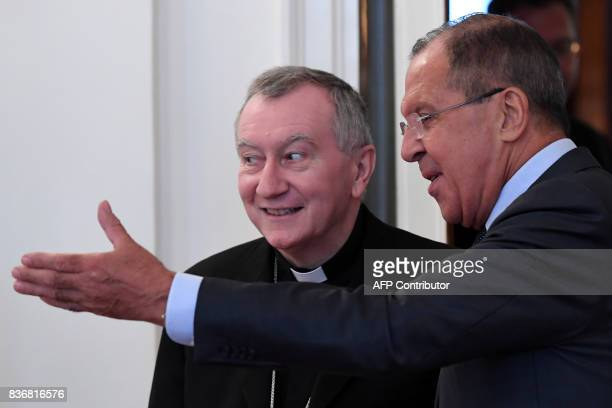 Russian Foreign Minister Sergei Lavrov shows the way to Vatican Secretary of State Cardinal Pietro Parolin during a meeting in Moscow on August 22...