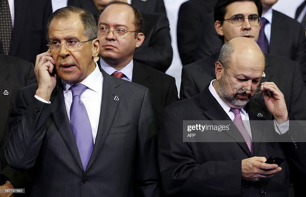 Russian Foreign Minister Sergei Lavrov (L) speaks on a mobile phone as Organisation for Security and Co-operation in Europe (OSCE) Secretary General Lamberto Zannier (R) checks his PDA during a group photo at the OSCE conference in Dublin December 6, 2012. The two day conference will be focusing on resolving conflict and improving the security and rights of the citizens of the OSCE. AFP PHOTO/POOL/Kevin Lamarque
