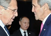 Russian Foreign Minister Sergei Lavrov speaks with US Secretary of State John Kerry as Russia's President Vladimir Putin stands behind during the UN...