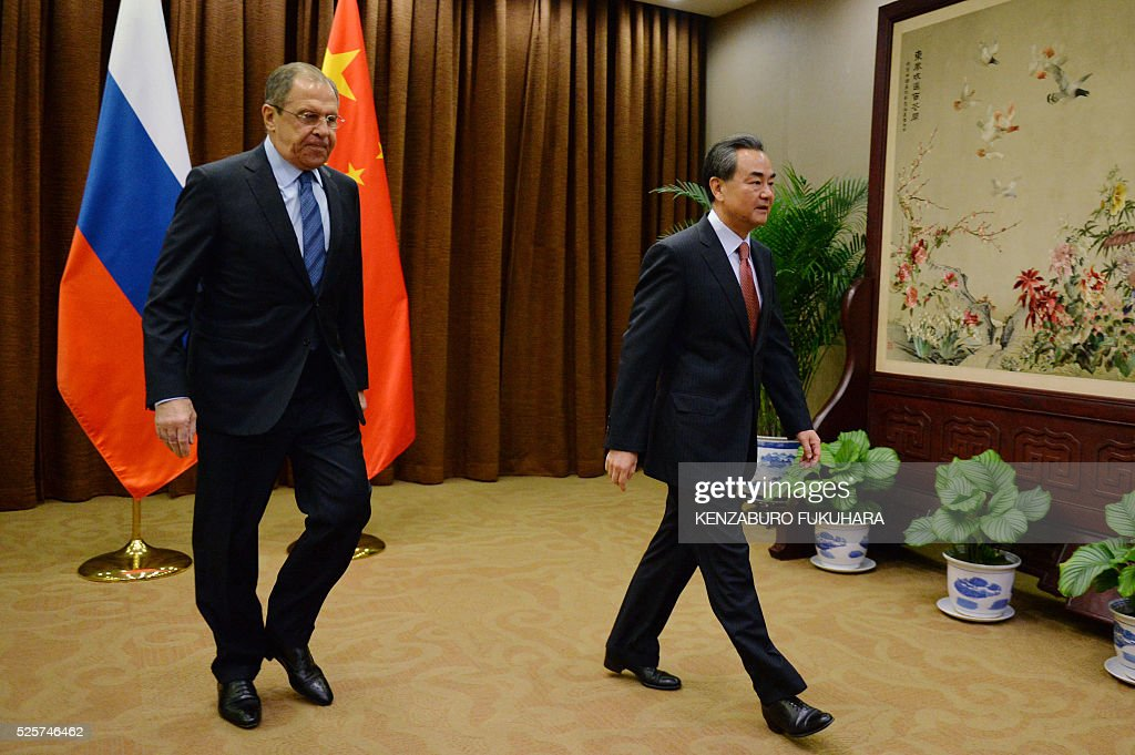 Russian Foreign Minister Sergey Lavrov (L) and Chinese Foreign Minister Wang Yi walk to their meeting at the Ministry of Foreign Affairs in Beijing on April 29, 2016. / AFP / POOL / KENZABURO