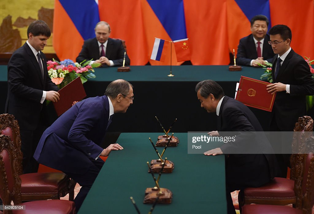 Russian Foreign Minister Sergey Lavrov (L) and Chinese Foreign Minister Wang Yi (R) take their seats before signing agreements as Russian President Vladimir Putin (back L) and Chinese President Xi Jinpin (back R) look on during a signing ceremony in Beijing's Great Hall of the People on June 25, 2016 in Beijing, China. Russian President Vladimir Putin is in China to discuss more economic and military cooperation between the two countries.