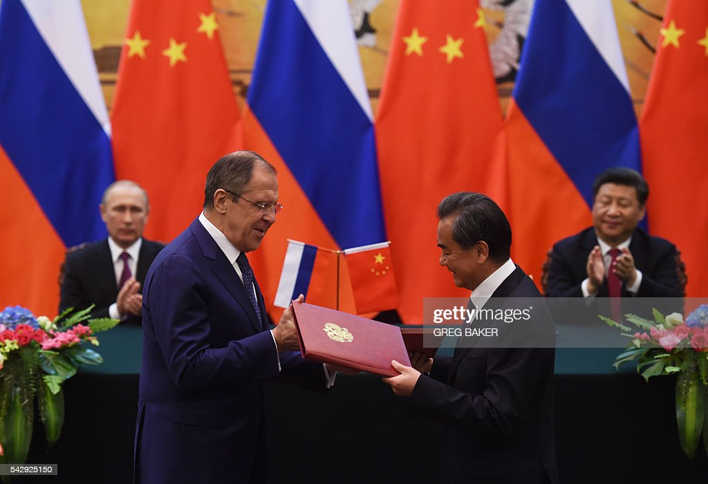 Russian Foreign Minister Sergey Lavrov (front L) and Chinese Foreign Minister Wang Yi (front R) exchange documents as Russian President Vladimir Putin (back L) and Chinese President Xi Jinping (back R) look on during a signing ceremony in Beijing's Great Hall of the People on June 25, 2016. / AFP / POOL / GREG