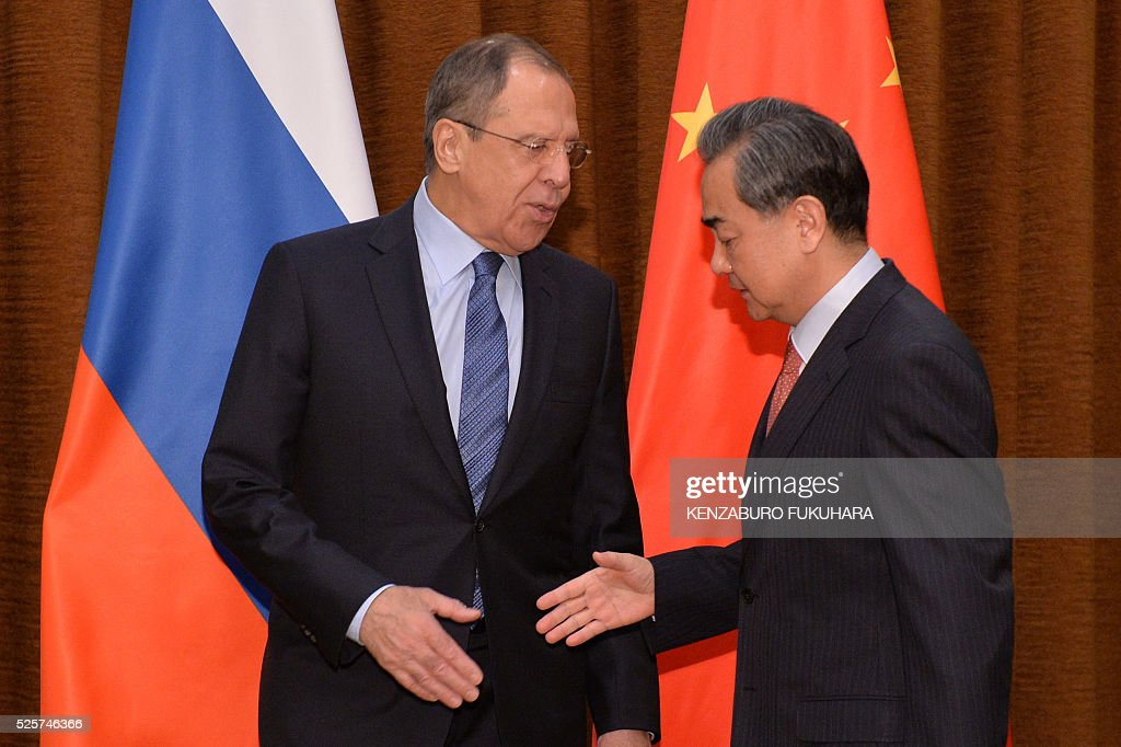 Russian Foreign Minister Sergey Lavrov (L) shakes hands with Chinese Foreign Minister Wang Yi before their meeting at the Ministry of Foreign Affairs in Beijing on April 29, 2016. / AFP / POOL / KENZABURO