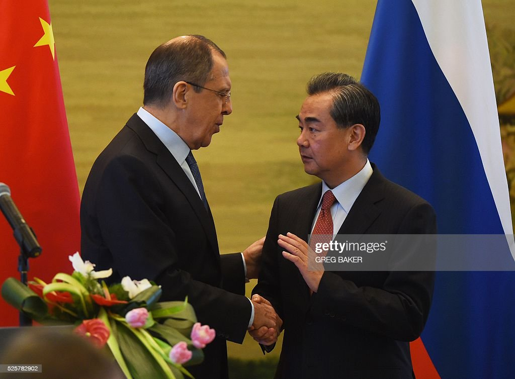 Russian Foreign Minister Sergey Lavrov (L) shakes hands with Chinese Foreign Minister Wang Yi after a joint press conference at the Ministry of Foreign Affairs in Beijing on April 29, 2016. / AFP / GREG