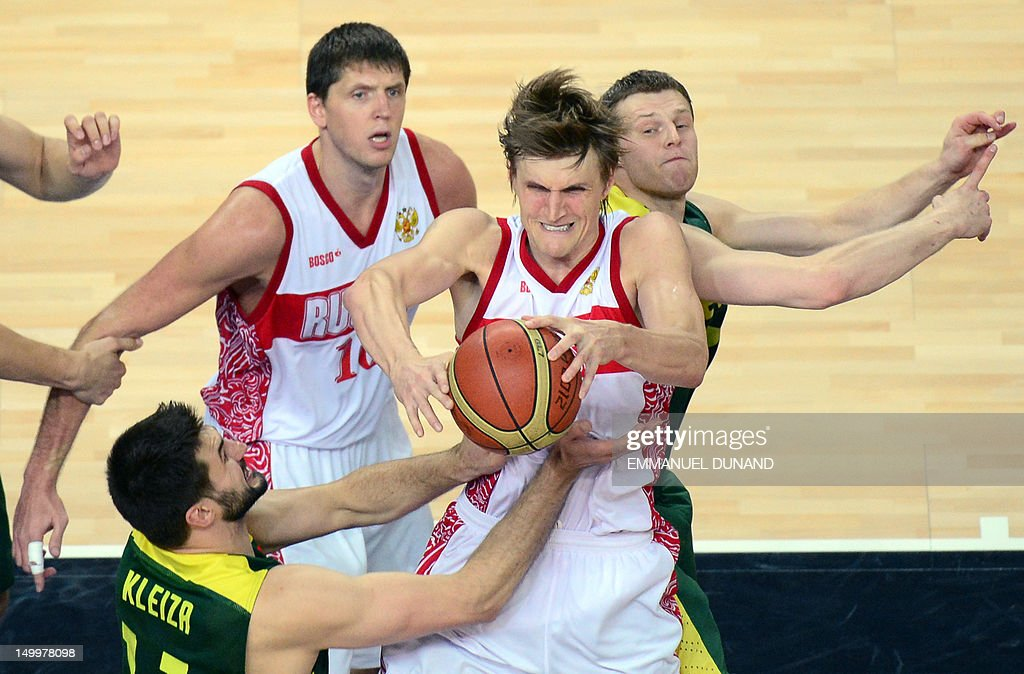 Russian forward Andrey Kirilenko (C) is challenged by Lithuanian forward Linas Kleiza (front) during their team's London 2012 Olympic Games men's quarterfinal basketball match in London on August 8, 2012.
