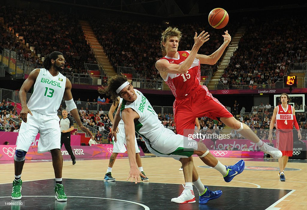 Russian forward Andrey Kirilenko (R) vies with Brazilian guard Anderson Varejao (C) and Brazilian centre Nene Hilario during the men's preliminary round Group A basketball match Brazil vs Russia of the London 2012 Olympic Games on August 2, 2012 at the basketball arena in London.