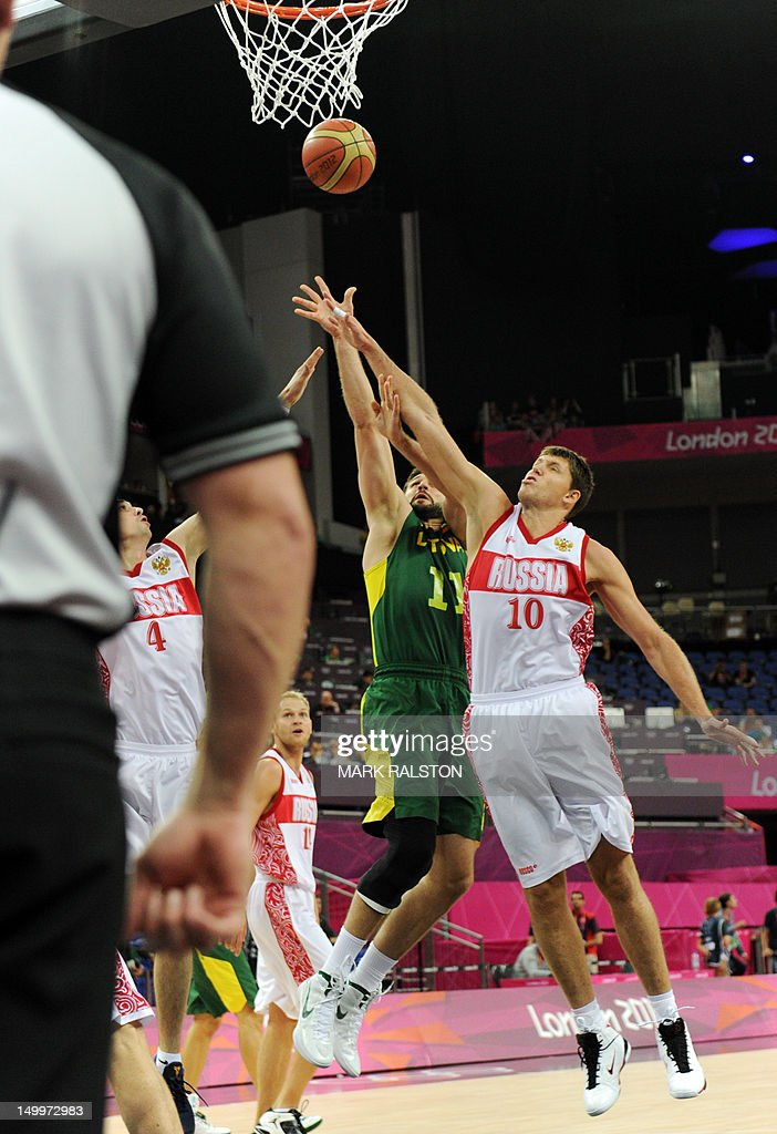 Russian forward Victor Khryapa (R) challenges Lithuanian forward Linas Kleiza during their London 2012 Olympic Games men's quarterfinal basketball match in London on August 8, 2012.