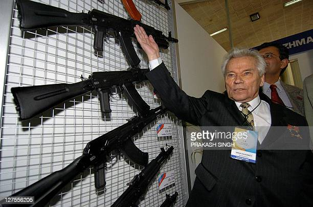 Russian inventor Mikhail Timofeevich Kalashnikov poses with AK series of assault rifles on the Russian Stand at the International Defence Exhibition...