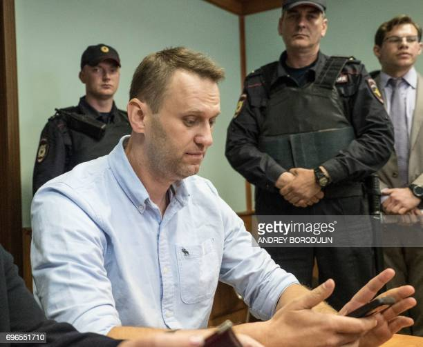 Russian jailed opposition leader Alexei Navalny checks his mobile phone as he attends a court hearing in Moscow on June 16 2017 Navalny has been...