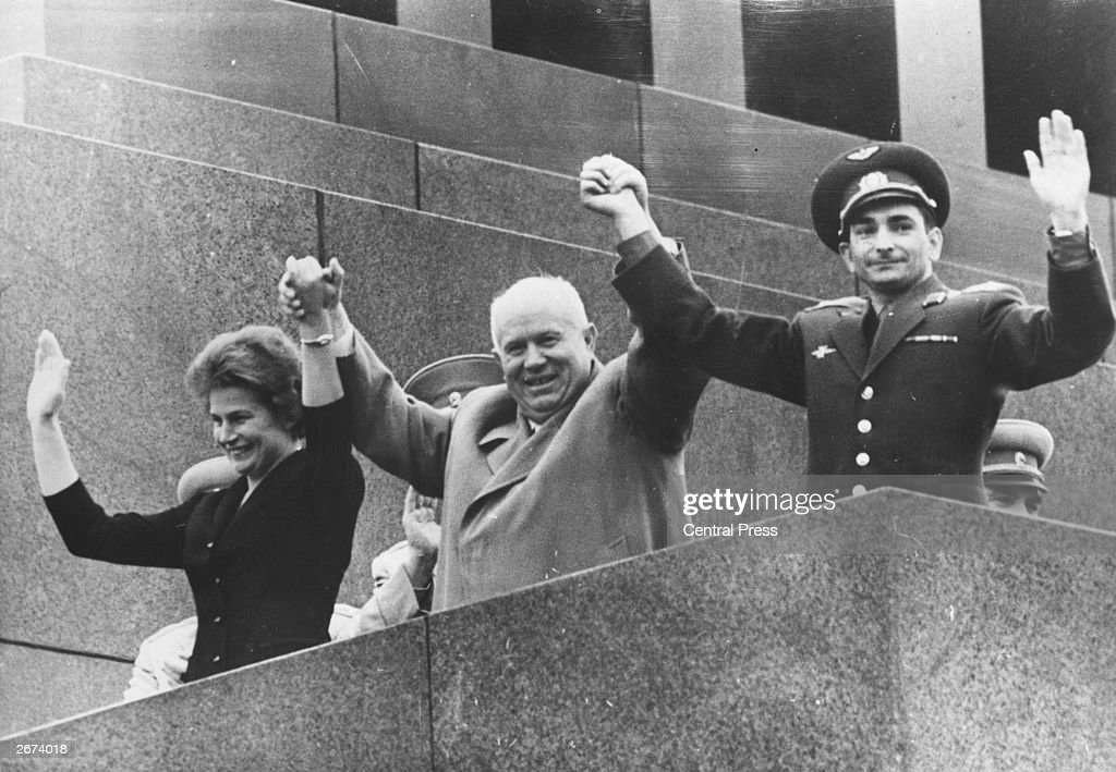 Russian leader Nikita Khrushchev (1894 - 1971) holds up the hands of Valentina Tereshkova, the first woman in space, and Valery Bykovsky, who holds the record for time in space, as Moscow welcomes the cosmonauts in Red Square.