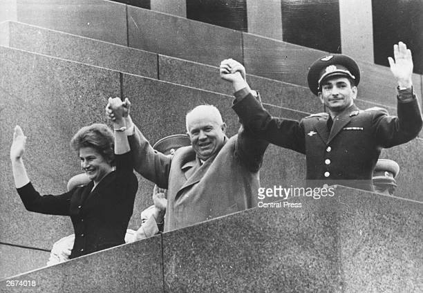 Russian leader Nikita Khrushchev holds up the hands of Valentina Tereshkova the first woman in space and Valery Bykovsky who holds the record for...