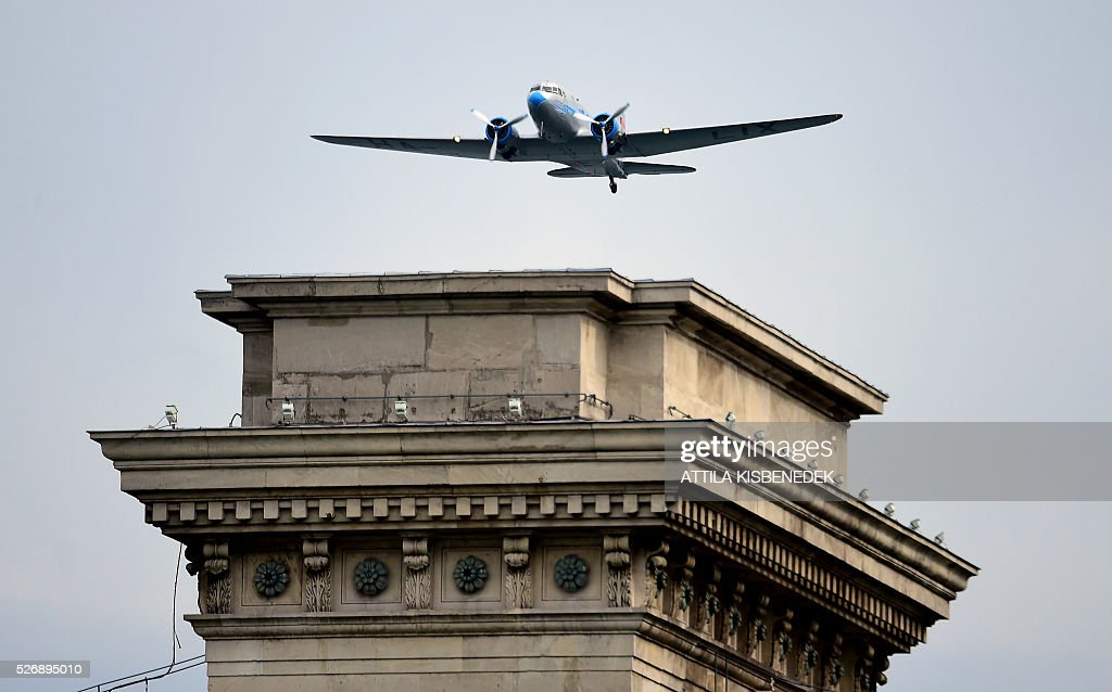 A Russian made Li-2 air plane flies over the oldest Hungarian bridge, the 'Lanchid' (Chain Bridge) of Danube River in Budapest on May 1, 2016 during the Budapest Air Show. / AFP / ATTILA