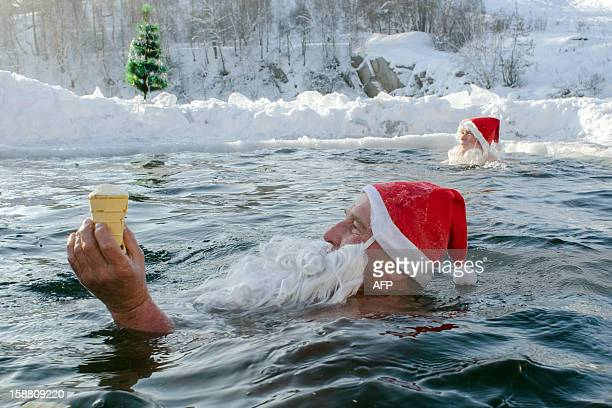 A Russian man holds an ice cream as he swims with other people dressed as Santa Claus in an icehole of a pond in the Siberian city of Novosibirsk on...