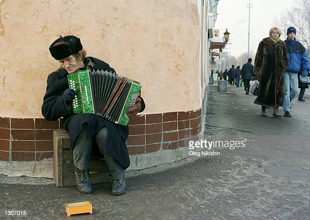 Russian man plays an accordion for money on the streets of Vologda about 450 km northeast of Moscow Russia November 26 2000