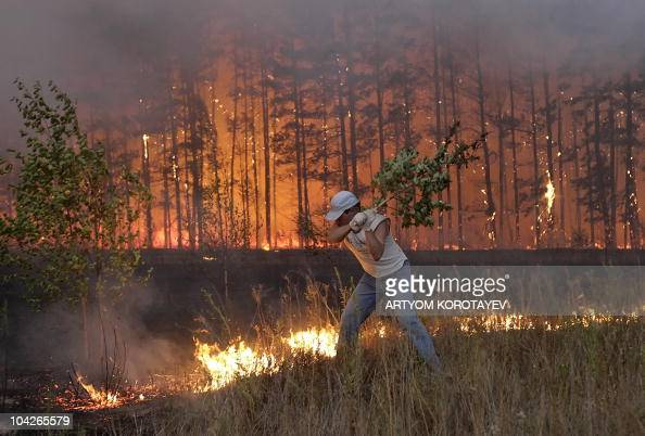 A Russian man tries to stop fire near village Dolginino on August 4 2010 Russia's worst heatwave for decades shows no sign of relenting officials...