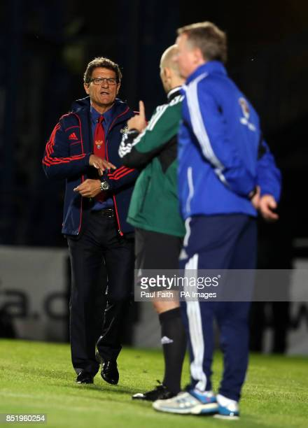 Russian Manager Fabio Capello checks the extra time with an offical during the 2014 FIFA World Cup Qualifier at Windsor Park Belfast