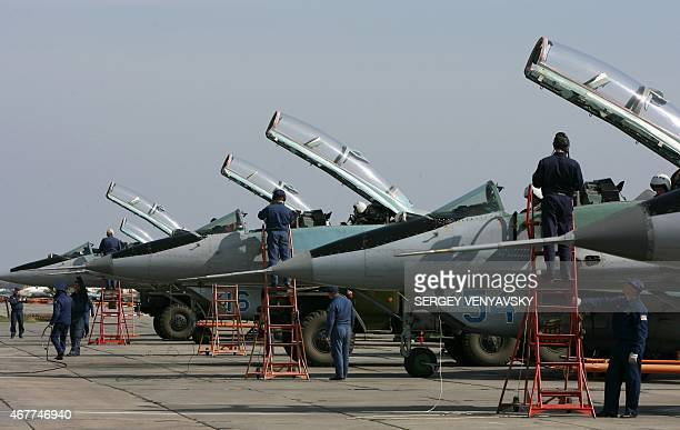 Russian military airforces technicians prepare MIG 29 jet fighters for a training session at PrimorksoAkhtarsk Krasnodar region on March 26 2015...