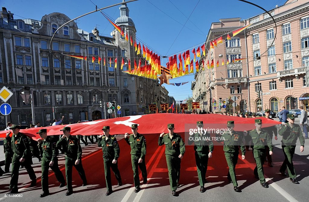 Russian military cadets carry a giant replica of the Soviet Banner of Victory during the Immortal Regiment march in central St. Petersburg on May 5, 2016. Russia will celebrate the 71st anniversary of the 1945 victory over Nazi Germany on May 9. / AFP / OLGA