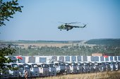 A Russian military helicopter flies over the trucks of Russian humanitarian convoy at a field outside the town of KamenskShakhtinsky in Rostov region...