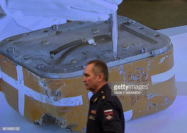 A Russian military official passes by a screen showing a live broadcast of the opening of the flight recorder from the Russian Sukhoi Su24 bomber...