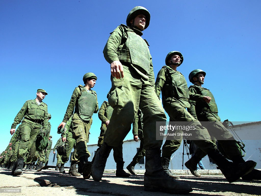 Russian military personnel walk around an Ukrainian military base on March 21, 2014 in Perevalne, Ukraine. Russian President Vladimir Putin signed a final decree on Friday, completed the legal process of making Crimea part of Russia.