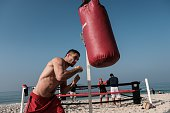 Russian MMA fighter Khetag Pilev hits a sandbag next to a beach boxing ring at Pepe beach in Rio de Janeiro Brazil on July 26 2016 Since boxing...