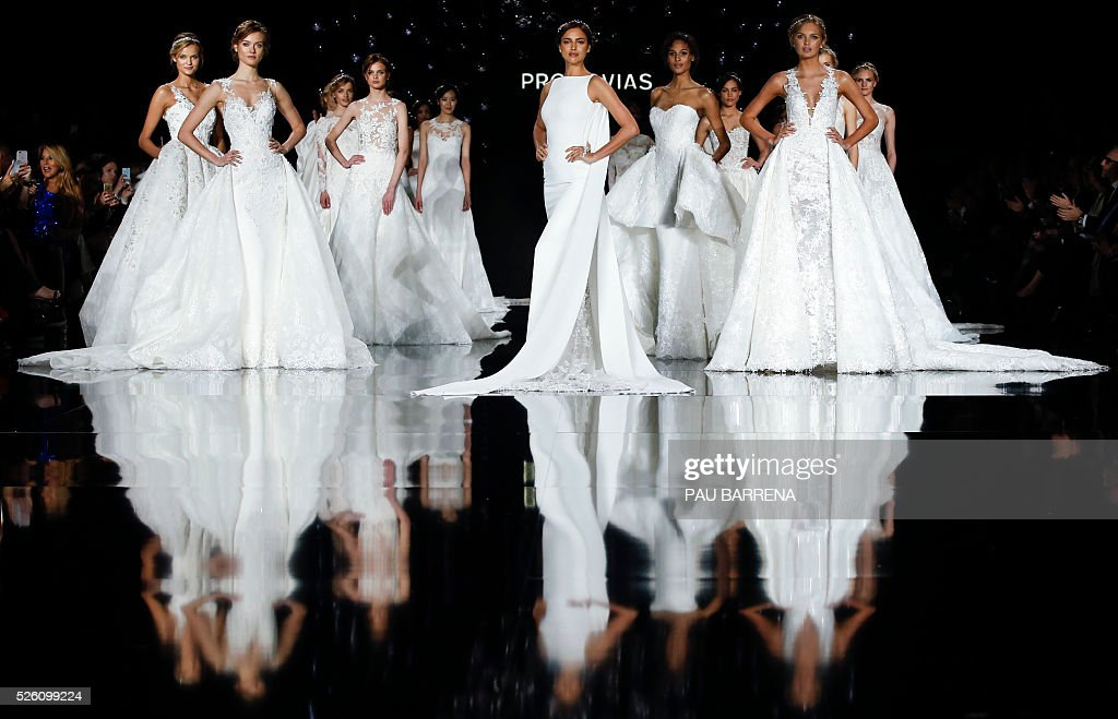 Russian model Irina Shayk (C) and other models present creations of the Pronovias 2016 collection during the last day of the Barcelona Bridal Week in Barcelona, on April 29, 2016. / AFP / PAU