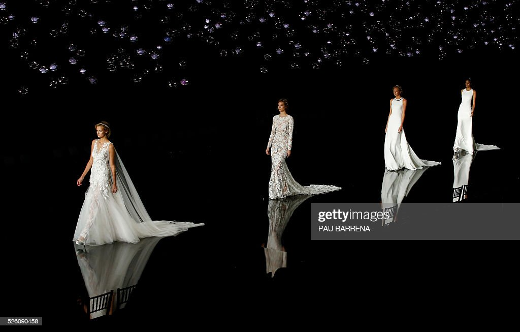 Russian model Kate Grigorieva, Polish model Jac Jagaciak, Dutch model Romee Strijd and French model Cindy Bruna present creations of the Pronovias 2016 collection during a press preview on the last day of the Barcelona Bridal Week in Barcelona, on April 29, 2016. / AFP / PAU
