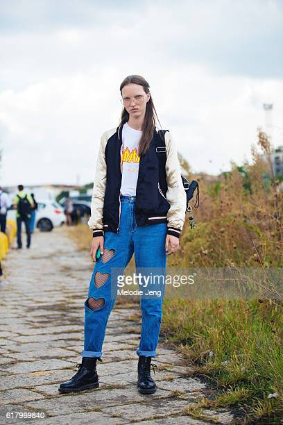 Russian model Liza Ostanina wears oversized clear glasses a souvenir/bomber jacket a Thrasher tshirt highwasted jeans with heart cutouts over fishnet...