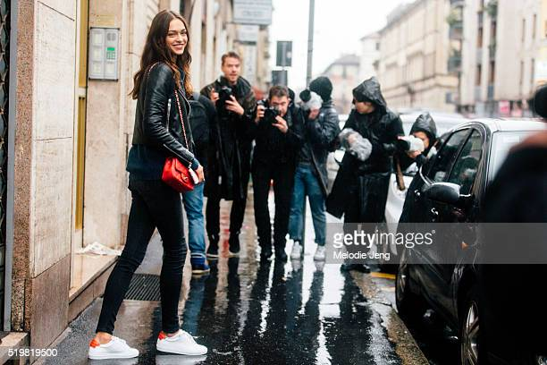 Russian model Zhenya Katava wears all black a red Chanel purse and red and white Adidas sneakers after the Dolce Gabbana show at Metropol during the...