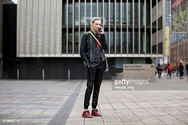 Russian model Zlata Semenko calls her driver in a black leather jacket and trousers gray sweater and maroon menswearinspired sneakers after the...