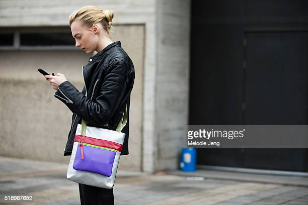 Russian model Zlata Semenko checks her phone and wears a black leather jacket with a metallic silver red and purple rectangular shaped purse at the...