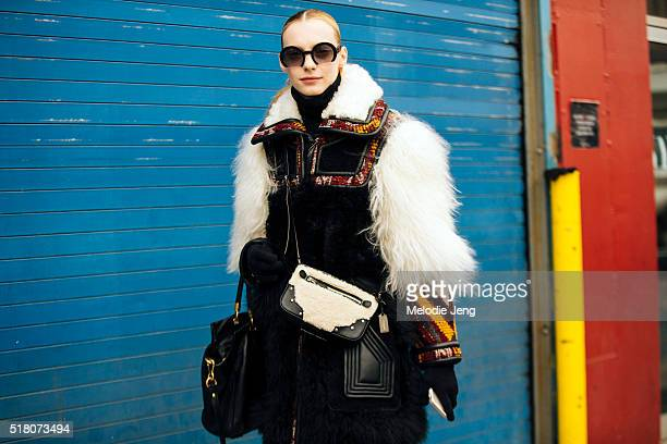 Russian model Zlata Semenko exits the Milly show at Pier 59 in coat with fur details and a leather and shearling small purse during New York Fashion...