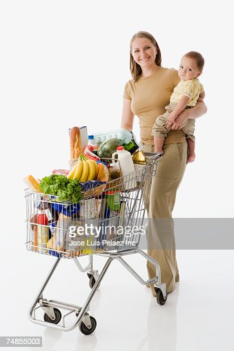 Russian mother holding baby and grocery shopping