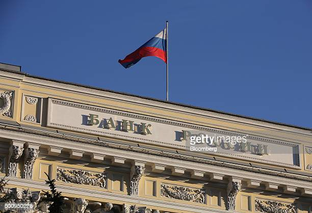 A Russian national flag flies above the headquarters of Bank Rossii Russia's central bank in Moscow Russia on Friday Dec 11 2015 Russia's central...