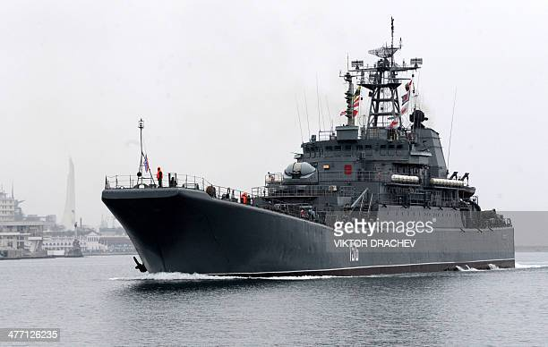 A Russian Navy ship sails to Sevastopol bay on March 7 2014 Trailed by a convoy of cars waving the Ukrainian flag and honking their horns two buses...