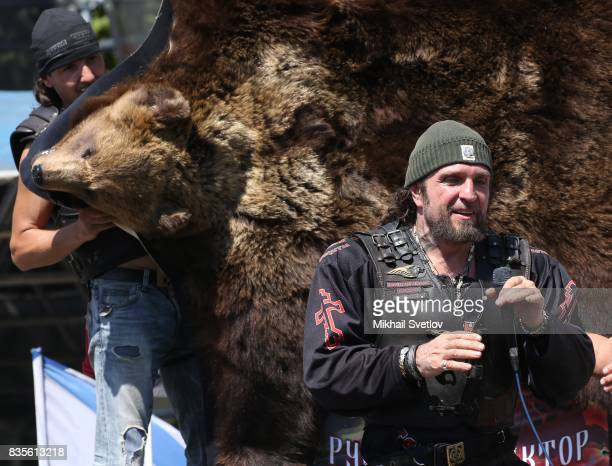 Russian Night Wolves Bikers Club Leader Alexander Zaldostanov also known as 'Khirurg' applauds as other biker holds a bearskin during the Sevastopol...