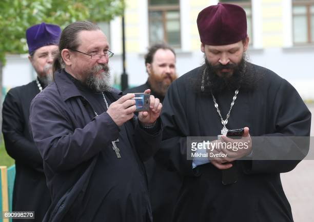 Russian OldRire Church belivers are seen in front of the Pokrovsky Cathedral while visiting Russian Orthodox OldRite priests take photos using their...