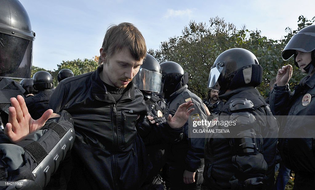 Russian OMON, riot police, officers detain a gay rights activist (L) during a gay pride event in Saint Petersburg on October 12, 2013. Russian police arrested today in the city of Saint Petersburg several people after clashes erupted between pro- and anti-gay demonstrators.
