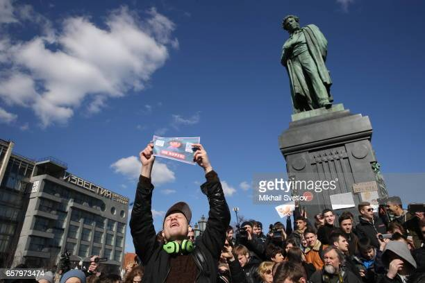 A Russian opposition activist holds a poster reading 'Cheater do not steal' during an unsanctioned protest rally in front of Pushkin monument at...