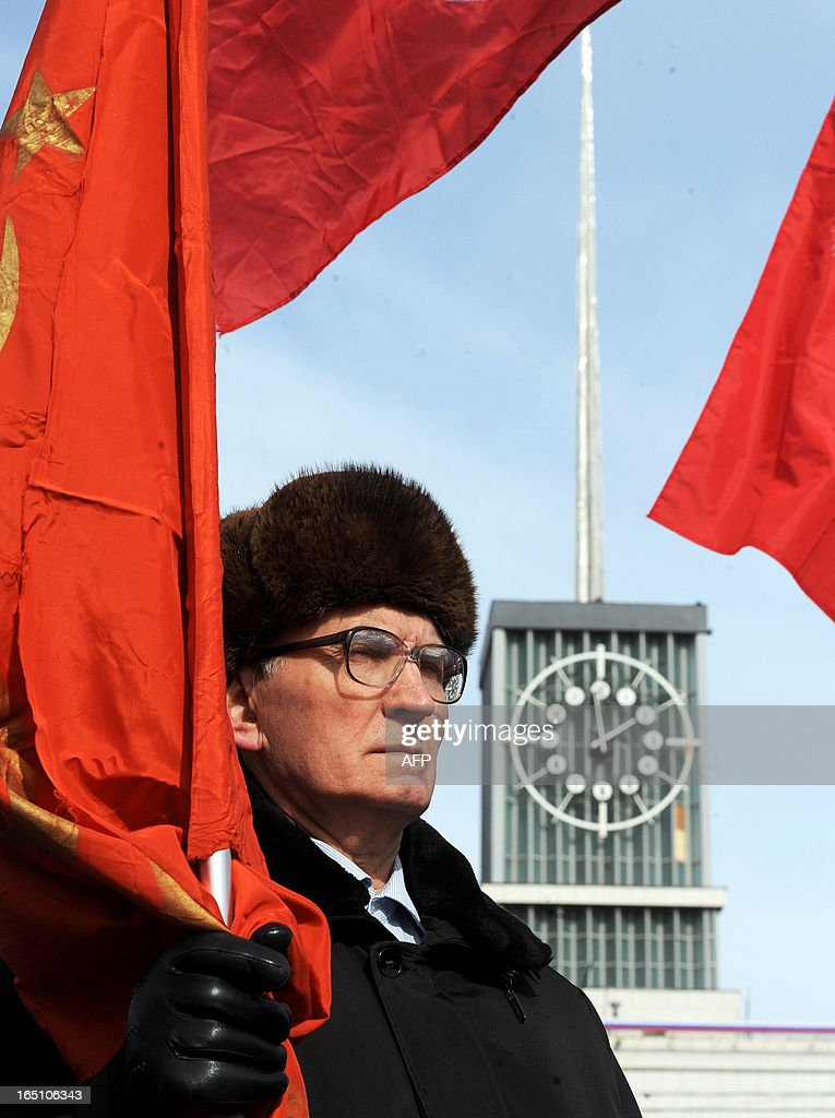 A Russian opposition supporter holds a red flag during a rally to protest against the increase of tariffs of housing and communal services in St. Petersburg on March 30, 2013. AFP PHOTO / OLGA MALTSEVA