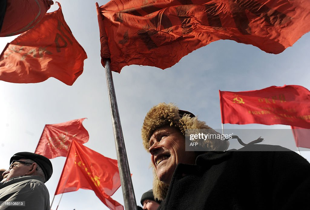 Russian opposition supporters hold red flags during a rally to protest against the increase of tariffs of housing and communal services in St. Petersburg on March 30, 2013.