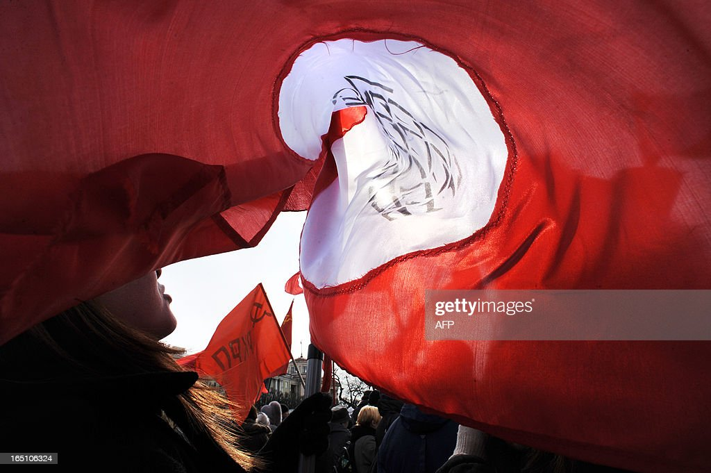 Russian opposition supporters hold red flags during a rally to protest against the increase of tariffs of housing and communal services in St. Petersburg on March 30, 2013. AFP PHOTO / OLGA MALTSEVA