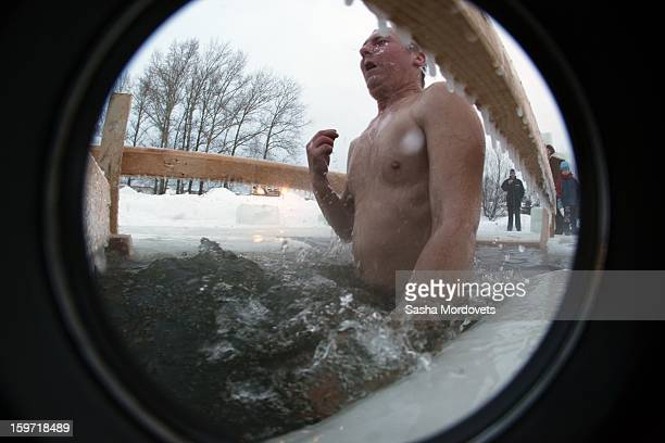 Russian Orthodox bathes in the icycold water of a lake during Orthodox Epiphany celebrations on January 19 2013 in the Yaroslavl region 260 km north...
