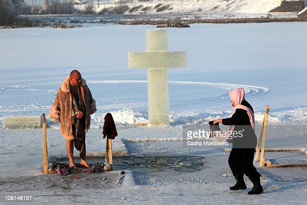 Russian Orthodox believer emerges from the icy water of a local river as air temperature is minus 10 Celsius during traditional Epiphany celebration...