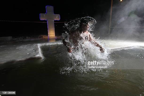 Russian Orthodox believer jumps out of the icy water in minus 15 degree Celsius temperatures during a traditional Epiphany celebration early January...