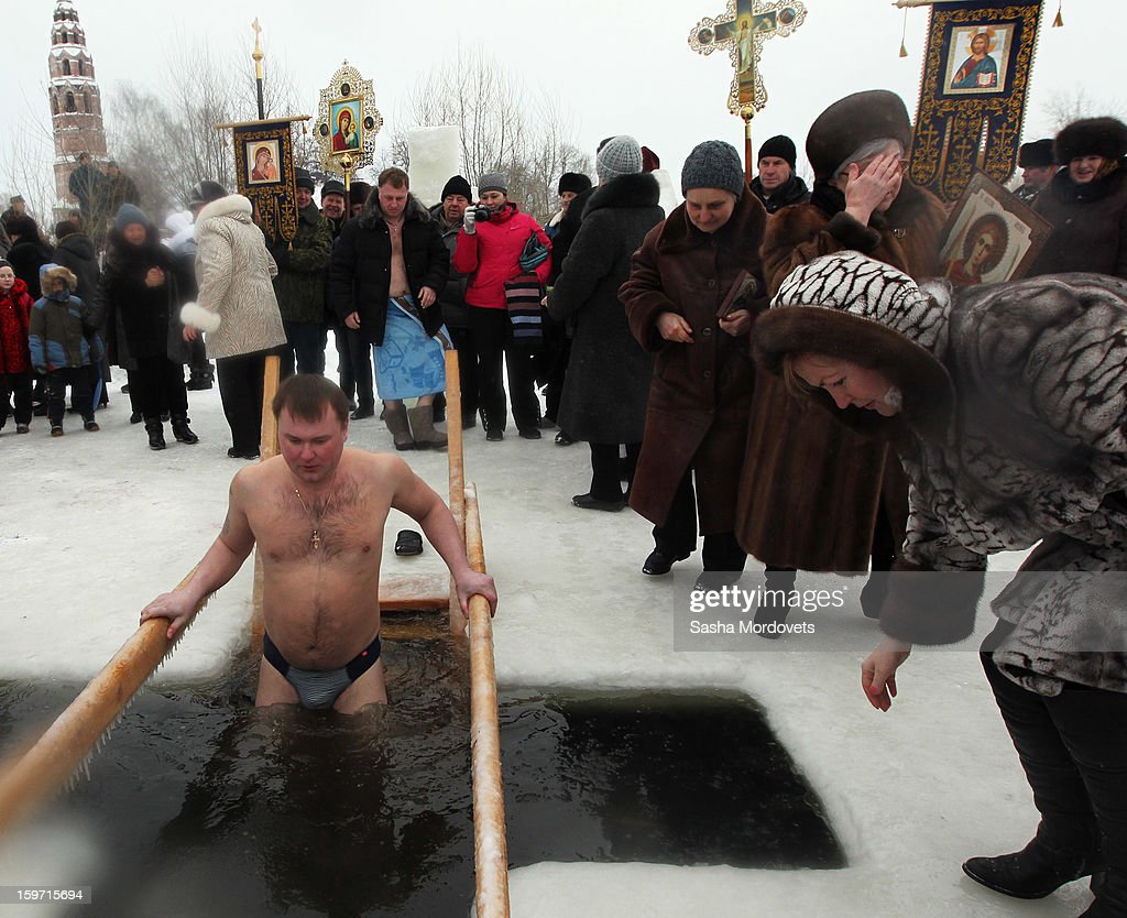 A Russian Orthodox believer lowers himself into the a crucifix-shaped hole cut into the ice during Orthodox Epiphany celebrations in the icy-cold water of the lake in Yaroslavl region, 260 km. North of Moscow on January, 19, 2013 in Russia. People all over Russia are taking part in a baptism ceremony, one the biggest events in the Christian Orthodox calendar.