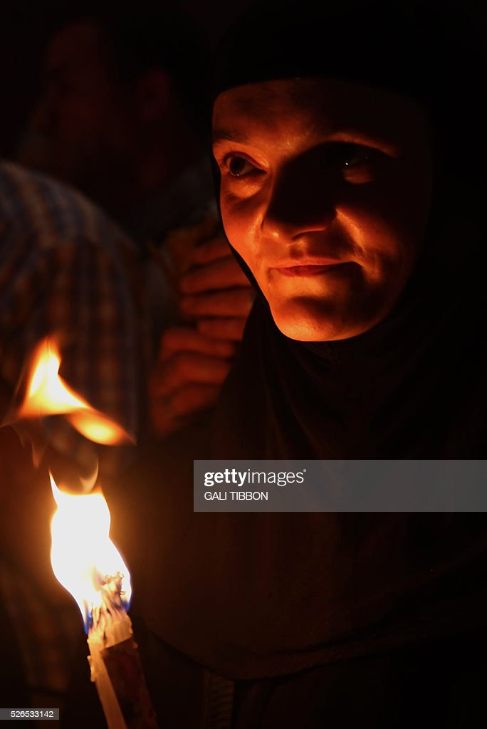 A Russian Orthodox nun hold up candles lit from the 'Holy Fire' as thousands gather in the Church of the Holy Sepulchre in Jerusalem's Old City on April 30, 2016 during the Orthodox Easter procession. The ceremony celebrated in the same way for eleven centuries, is marked by the appearance of sacred fire in the two cavities on either side of the Holy Sepulchre. / AFP / GALI