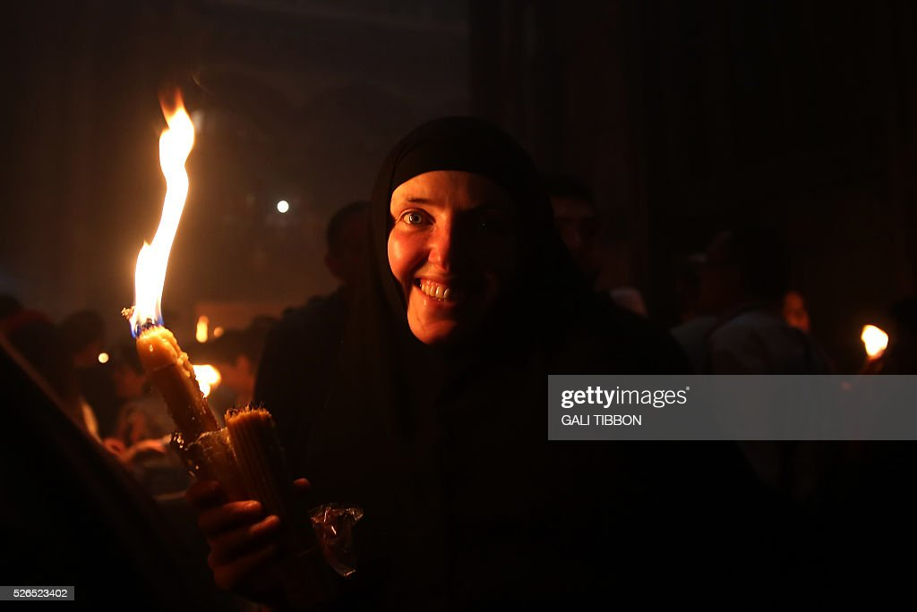 A Russian Orthodox nun holds candles lit from the 'Holy Fire' as thousands gather in the Church of the Holy Sepulchre in Jerusalem's Old City on April 30, 2016 during the Orthodox Easter ceremony. The ceremony celebrated in the same way for eleven centuries, is marked by the appearance of sacred fire in the two cavities on either side of the Holy Sepulchre. / AFP / GALI